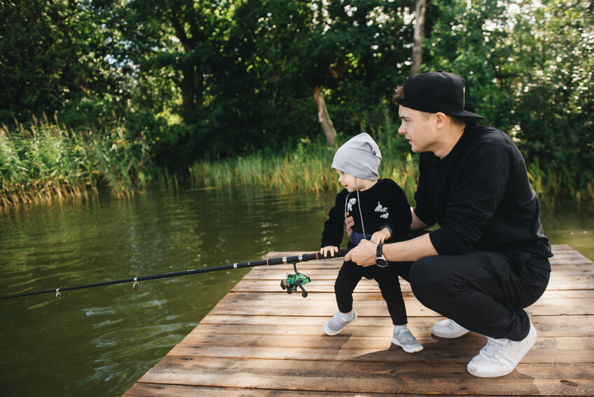 Father and cute one-year-old son fishing with a fishing rod in nature. The concept of rural getaway. Article about fishing day.